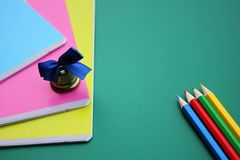Bell and school notebooks are located on a green background next to colored pencils stock image