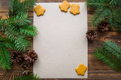 Bell shape Christmas cookie and fir tree branches frame. Mock-up. Free place for text. Brown wooden background. Copy-space. Bell shape Christmas cookie and fir stock images