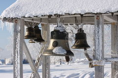 Bell in the snow near the temple in the winter. Belfry with bells in the snow against the blue sky Stock Photo