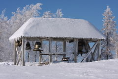 Bell in the snow near the temple in the winter. Belfry with bells in the snow against the blue sky Royalty Free Stock Photos