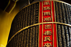 The Bell of Temple. There are eight chinese words with the red background beside the bell it mean Good Crop Weather, The Peaceful Country and Safe People Royalty Free Stock Photos
