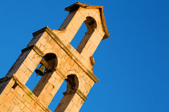Bell tower. Fragment of an old bell tower against a clear blue sky Stock Image