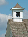Bell tower. Schoolhouse bell tower against a cloudy blue sky stock image