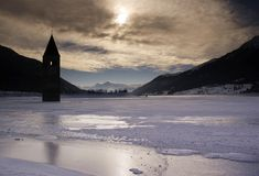 Bell Tower. It shows a a bell tower of a church which is standing in a lake with view to the highest montains in Italy Royalty Free Stock Photos