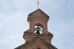 Bell tower of the chapel with bell, cross and vane. Bell tower of the place dedicated to the religious cul stock photography
