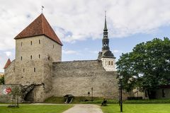 The bell tower of the Church of St. Nicholas appears behind the towers and medieval walls of the Old Town of Tallinn, Estonia stock photos