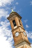 Bell tower with a clock. Of italian church on the blue sky stock images