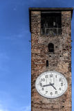 Bell tower with clock. Ancient bell tower made of bricks with a clock with a clean and blue sky on the background Royalty Free Stock Photos