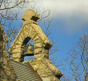 Bell tower of Country church. A small country church in a state park.  interesting shades of brown.  the bell tower and stone cross finish the top of the Stock Image