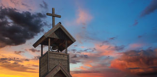 A Bell Tower with Cross at Sunset Stock Photography