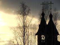 Bell tower and domes. Bell tower and dome of the church with crosses and tops of trees growing nearby at sunset Stock Photo