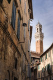 Bell Tower framed by ancient houses. A bell tower of an ancient Tuscan town, surrounded by ancient houses Royalty Free Stock Photo
