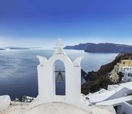 The bell tower of Greek Orthodox Church on the background waters of the Aegean sea in Oia town on Santorini island Stock Images