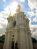 Bell tower of Kiev-Pechersk Lavra with bright sun on blue sky with white clouds. Stock Photo