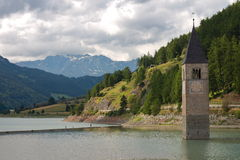 Bell tower in a lake on the Alps. Lake with an awash bell tower royalty free stock photos