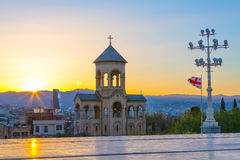 Bell tower near Holy Trinity church sunset panorama in Tbilisi, Georgia stock images