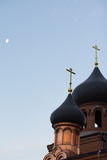 Bell tower of old believer orthodox church at early winter morning, crosses with moon in the sky. Vertical Stock Photos