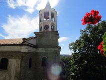 Bell tower and red flower stock photography