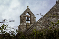 Bell tower on an old, rural, stone church. The bell is visible from the countryside on this traditional, old, stone church Stock Images