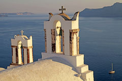Bell tower of old white church above the beautiful blue sea, Oia Royalty Free Stock Images