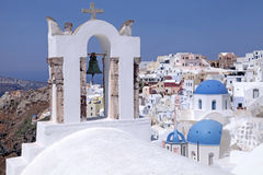 Bell tower and orthodox church,  Oia, Santorini island, Greece. View with bell tower and white and blue orthodox church in the village of Oia, Santorini island Royalty Free Stock Images