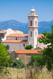 Bell tower of Piana, South Corsica, France. Small Corsican village vertical landscape, old living houses with red tile roofs and bell tower. Piana, South Corsica Stock Images