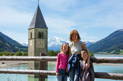 The bell tower in Reschensee and family (Italy). Stock Photography