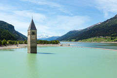 The bell tower in Reschensee and family (Italy). Royalty Free Stock Photo