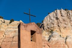 Bell tower and rustic wood cross underneath high colorful cliffs topped by a group of three crosses. Bell tower and rustic wood cross of an adobe church and royalty free stock image