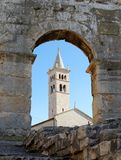 Bell tower of Saint Anthony Church in Pula, Croatia. Seen through the arc of Pula Amphitheater Royalty Free Stock Photos
