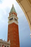 Bell tower of Saint Mark with the Arch of the Ducal Palace. In venice Royalty Free Stock Image