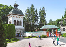 The bell tower of Sinaia monastery and the yard filled with tourists Stock Image