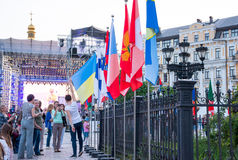Bell tower of St. Sophia Cathedral, stage and flags of countries. People are photographed with the flag of Ukraine. Bell tower of St. Sophia Cathedral, stage and Royalty Free Stock Images