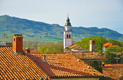 The bell tower and tiled roofs, mountains in the background Stock Images