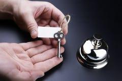 Bell und der Schlüssel an der Aufnahme im Hotel Lizenzfreie Stockfotos