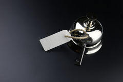 Bell und der Schlüssel an der Aufnahme im Hotel Stockfotografie