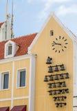 Bell und Uhr auf alter gelber Kirche Stockfotografie