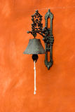 Bell on a wall. Old vintage bell on a orange wall stock image