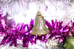 Bell on white Christmas tree covered in tinsil Royalty Free Stock Photo
