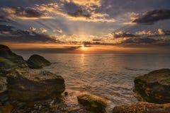 Bella alba dell'oceano - il mare calmo ed i massi con il cielo espongono al sole il Ra Fotografie Stock Libere da Diritti
