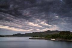 Bella alba lunatica sopra il lago calmo con la barca sulla riva Immagine Stock