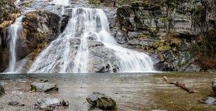 Bella ampia cascata con un foro di nuoto nella priorità alta nel primo mattino in Svizzera del sud Fotografia Stock