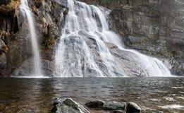 Bella ampia cascata con un foro di nuoto nella priorità alta nel primo mattino in Svizzera del sud Immagine Stock