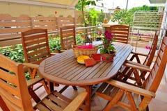 Bella area all'aperto con la tavola e le sedie di legno fotografia stock libera da diritti