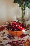 Bella arte, aún composición de la vida con las cerezas rojas frescas de las bayas de un marsala en placa anaranjada del pueblo en Fotos de archivo