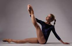 Bella ballerina con l'ente perfetto in attrezzatura blu in studio Immagini Stock