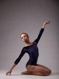 Bella ballerina con l'ente perfetto in attrezzatura blu sul fondo grigio dello studio sulle sue ginocchia, una mano su Immagine Stock