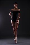 Bella ballerina della donna nel vestito del corpo nero che posa sulle dita del piede più Fotografia Stock