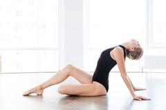 Bella ballerina della giovane donna che si siede e che allunga a scuola di balletto Fotografie Stock Libere da Diritti