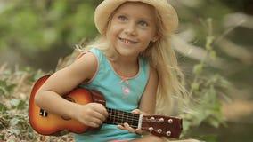 Bella bambina in cappello di paglia che gioca sul giocattolo video d archivio